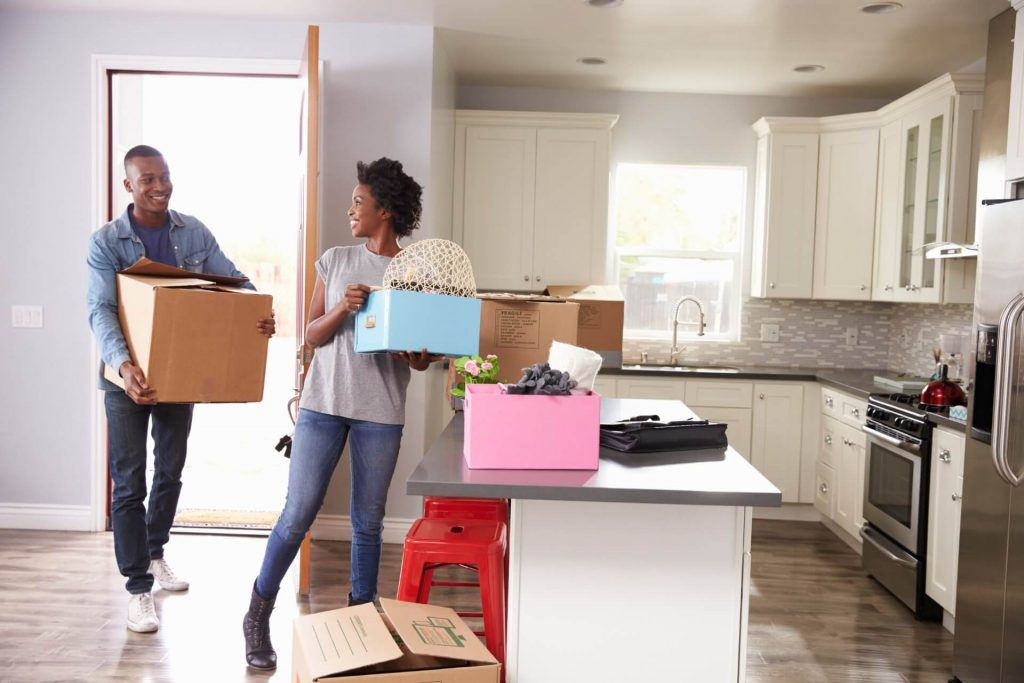 a young couple holding boxes moving in their new home