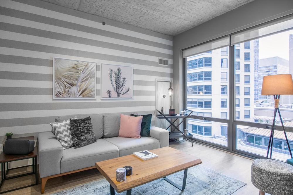 A living room area in Chicago with a grey couch, wooden coffee table and a bar cart in the corner. There is a grey footstool next to a lamp on the opposite side of the room. One wall is completely made of glass and offers a view of the city