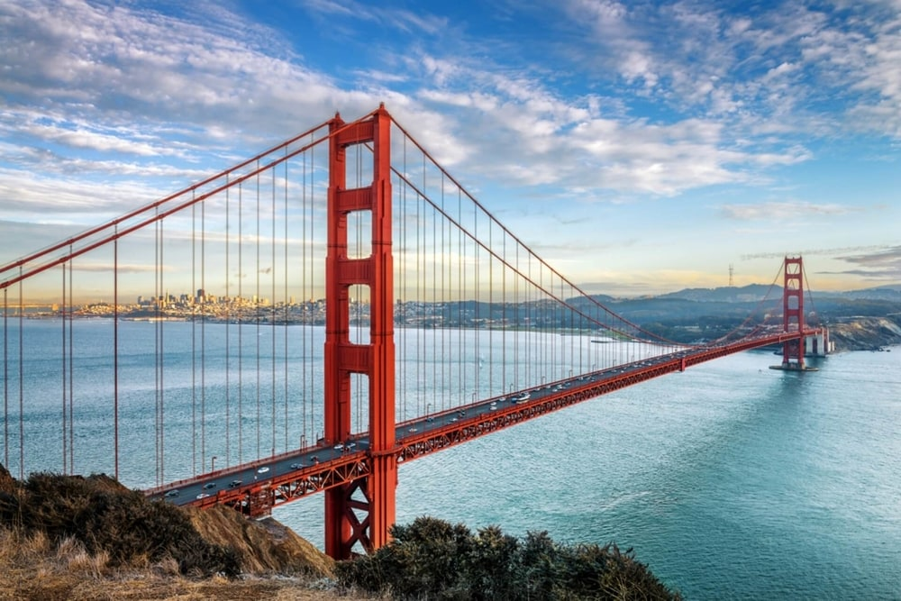 a view of golden gate bridge with a blue sky and white clouds