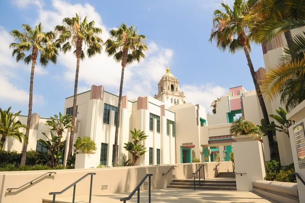 The Beverly Hills City Hall building in California is white and blue and pink with a bell tower structure at the top and palm tress all around. There are some stairs in the foreground of the photo leading up to the entrance.