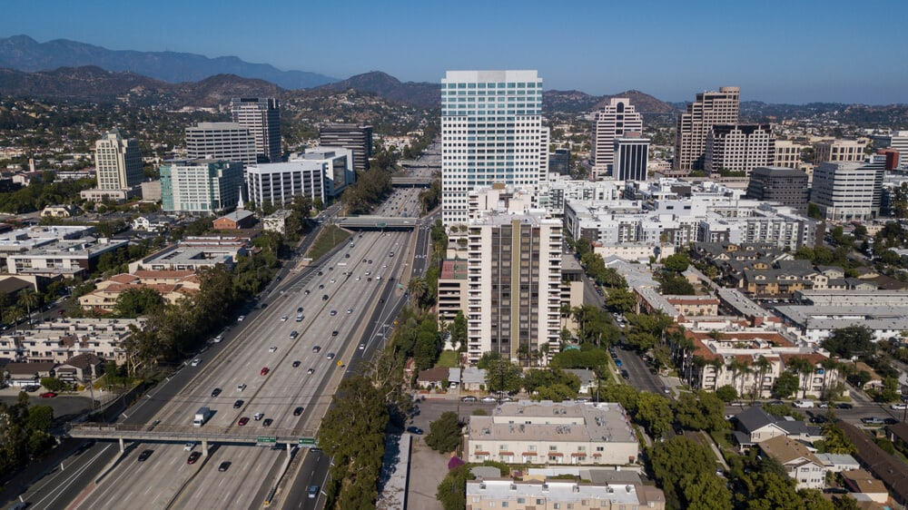 A large highway with many cars on it with tall buildings on either side. It is a view of Glendale, California from above.