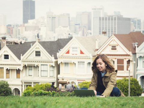 housing San Francisco Young girl sitting on a lap top on a lawn in front of traditional San Francisco style housing