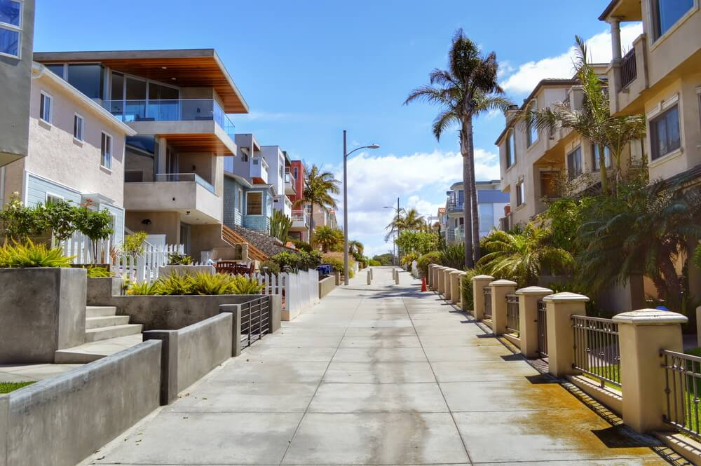 A pathway between rows of houses to walk down to the ocean in the Manhattan Beach neighborhood of Los Angeles California