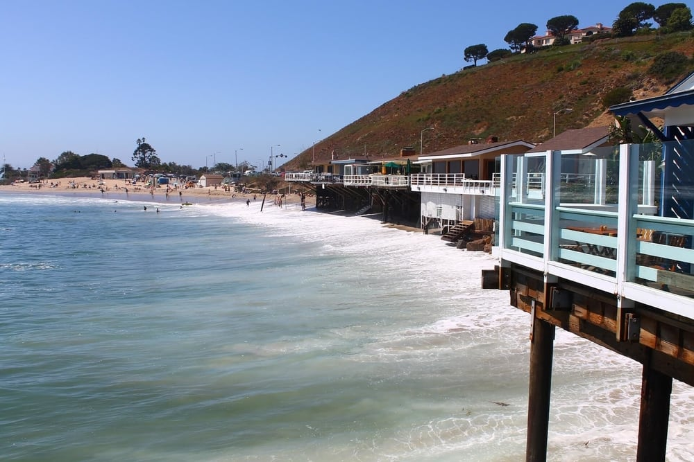 A beach view in Marina Del Ray, Los Angeles with the waves crashing agains the side of the mountain with luxury properties along the side and a sandy beach full of people in the top left corner under a blue sky