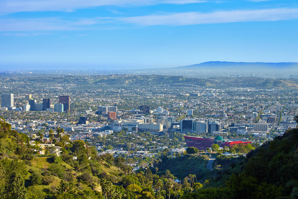 A panoramic view from above of West Hollywood. There are many buildings among the green tress with a deep blue sky above and some mountains out in the distance.