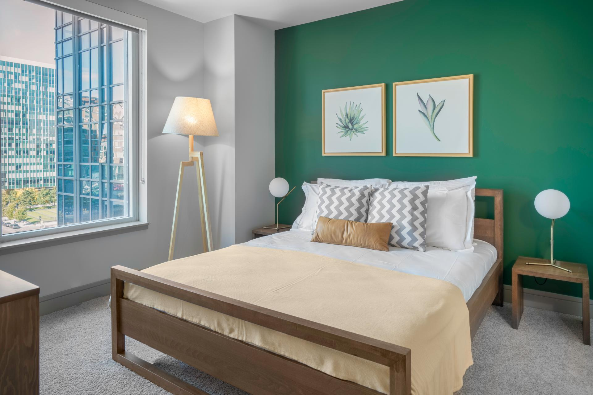 blueprint blueground one bedroom apartment Boston bedroom with wooden bedframe against green walls