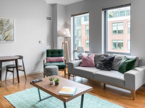 blueprint blueground one bedroom apartment Boston furnished living room with wooden dining set and green pink and grey themed furniture