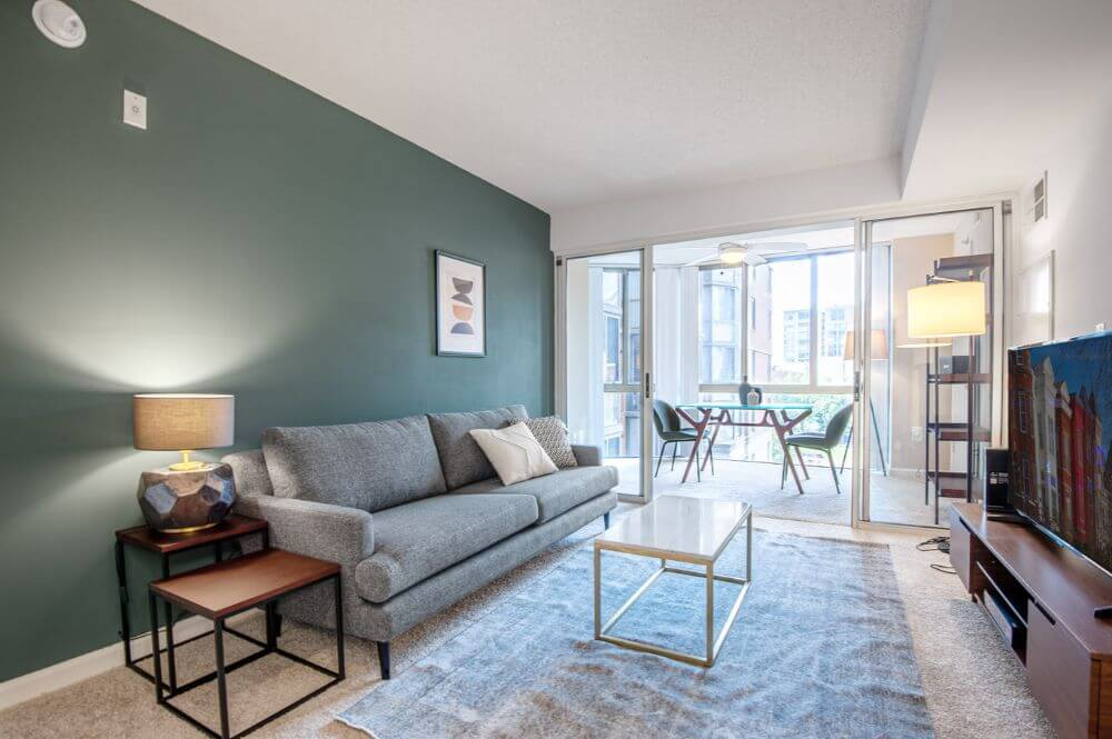 A furnished and equipped apartment in DC that is managed by Blueground. There is a dark green wall behind a grey couch as well as a coffee table, TV and a dining area to the right