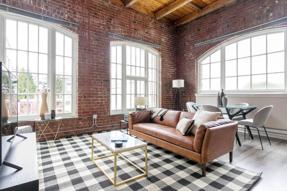a leather sofa next to a coffee table on top of a black and white chequered carpet inside a brick wall apartment with three big windows with white window panes